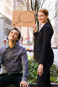 Woman holding thought bubble over man