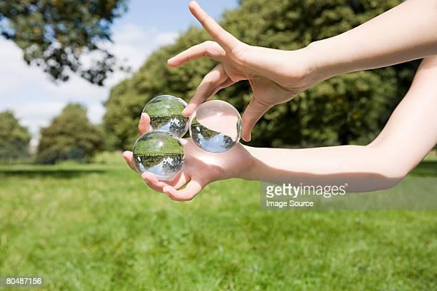 Mujer agarrando tres pelotas de vidrio