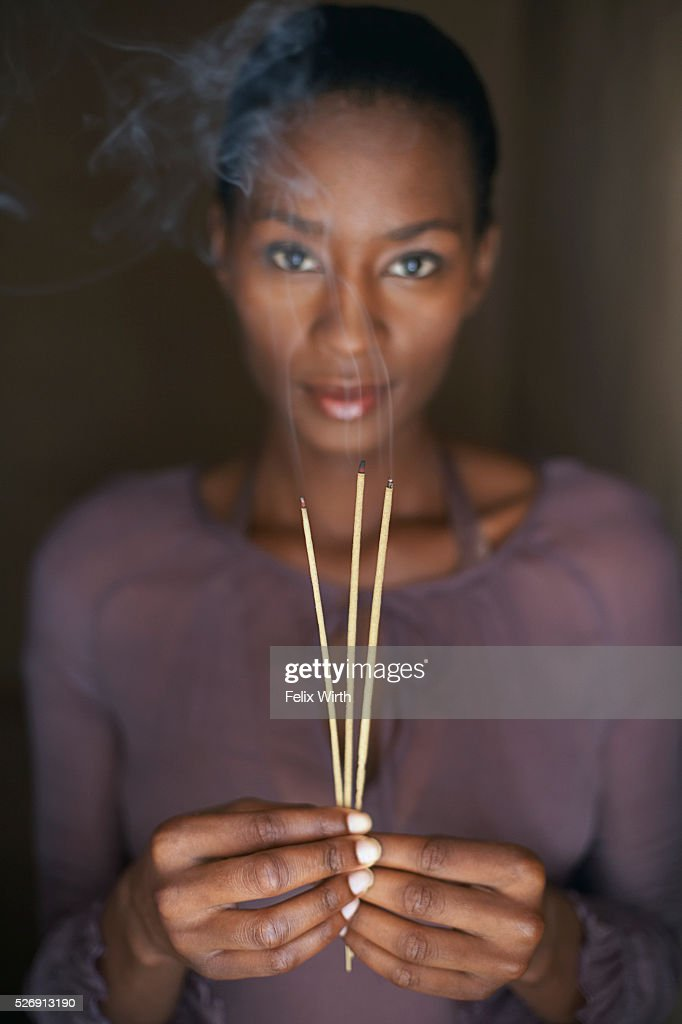 Woman holding three sticks of incense : Stock-Foto