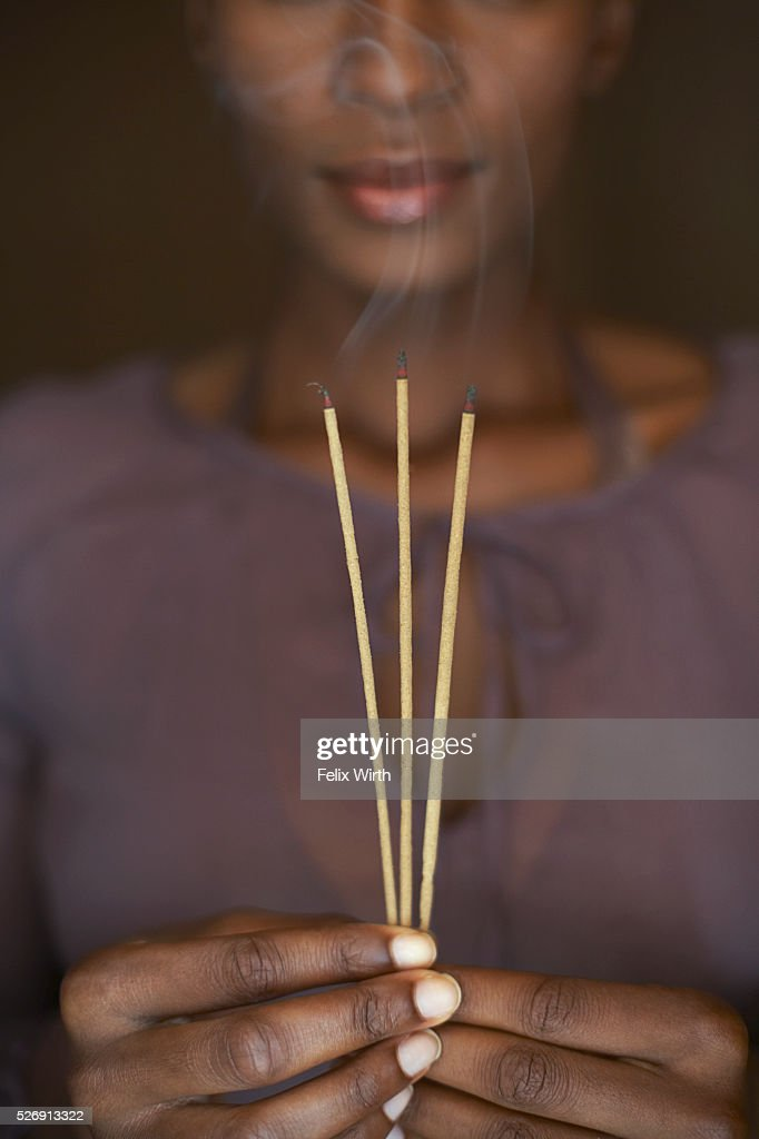 Woman holding three sticks of incense : Foto de stock