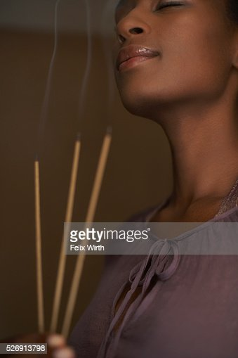 Woman holding three sticks of incense : Stockfoto
