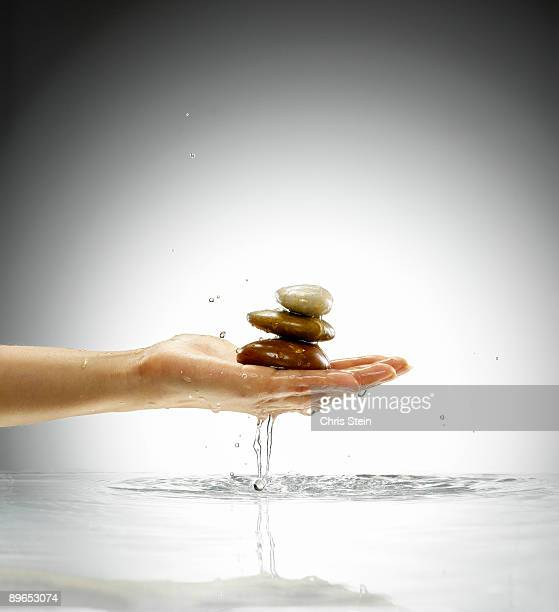 Woman holding three stones