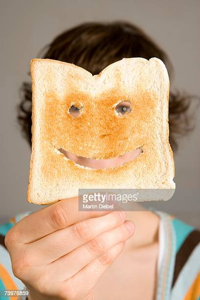Woman holding toast in front of face