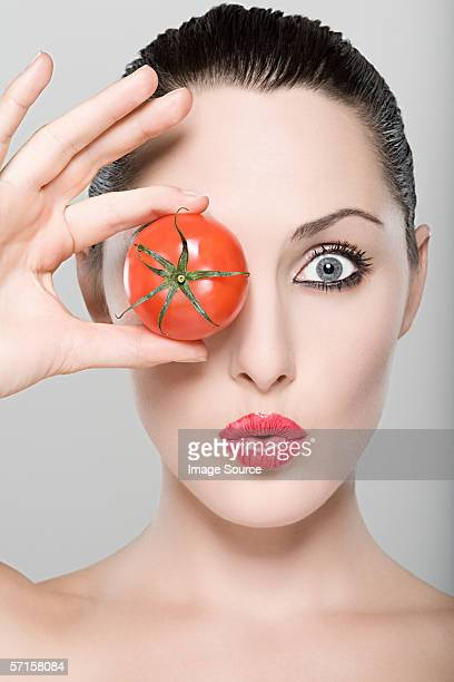 Frau mit Tomaten über Auge