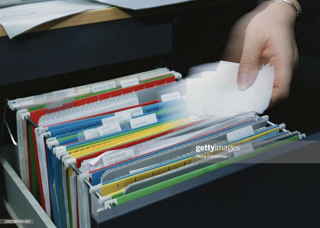 Woman holding torn paper over file drawer (blurred motion) : Stock Photo