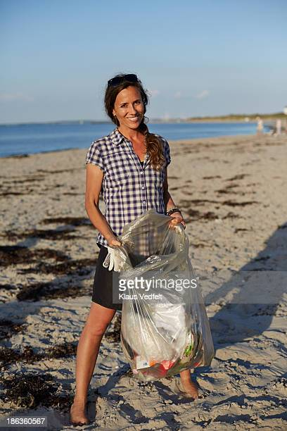 Woman holding trash bag on beach and smiling