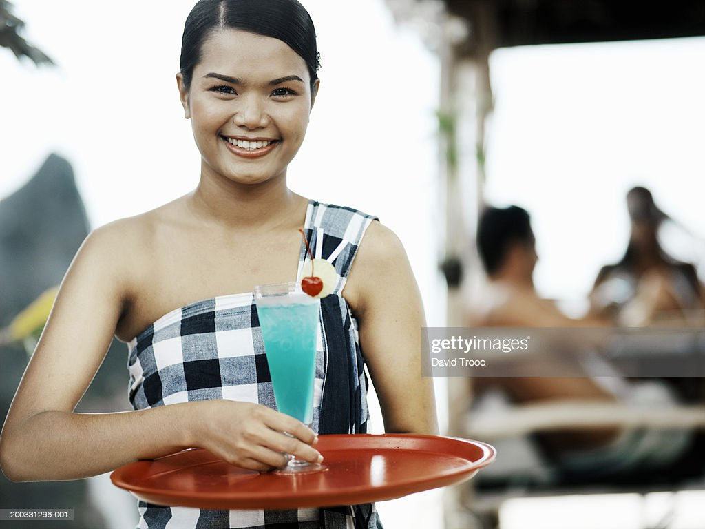 Woman holding tray and cocktail, smiling, portrait