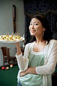 Woman holding tray of appetizers, smiling at camera