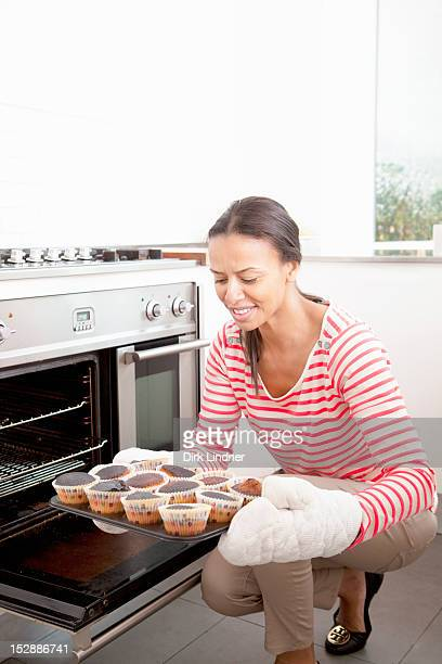 Woman holding tray of burned cupcakes