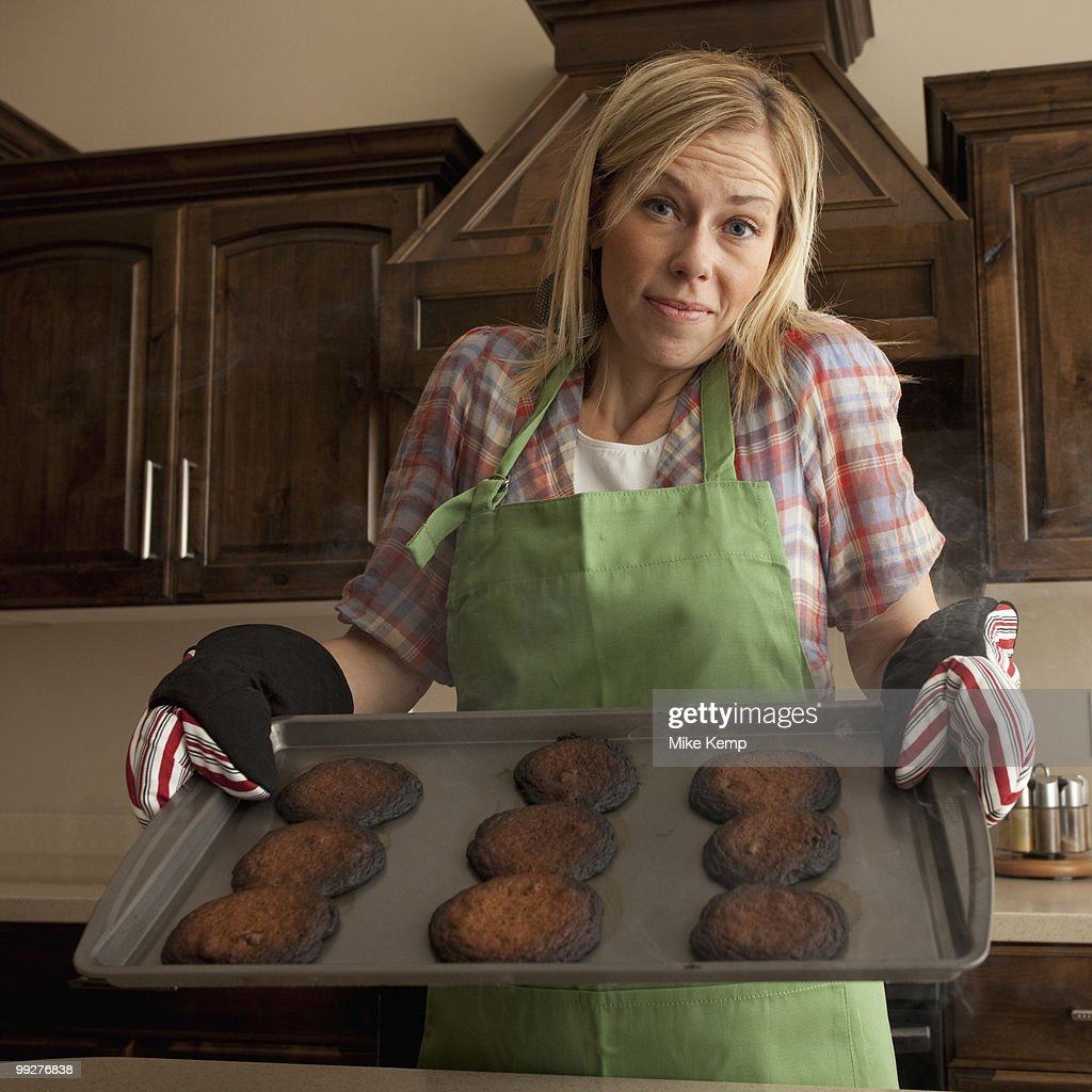 Woman holding tray of burnt cookies