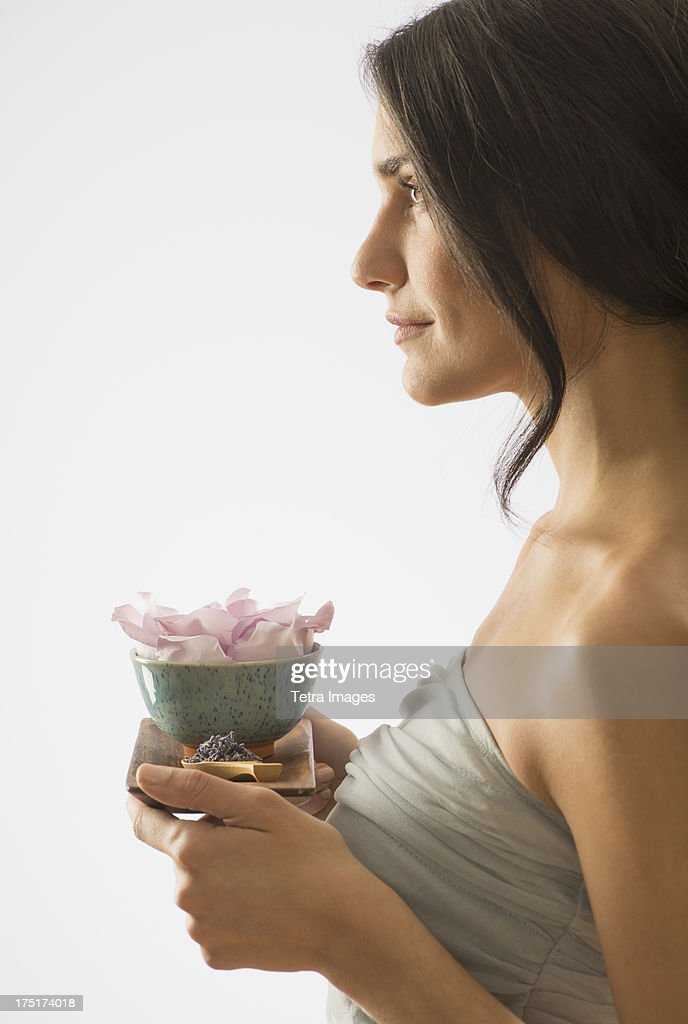 Woman holding tray with scented flower