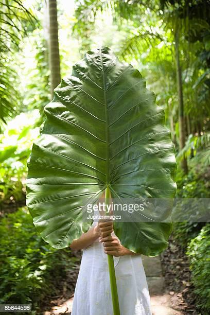Woman holding tropical leaf