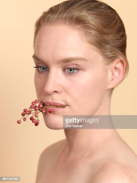 woman holding twig with red berry like fruit in her mouth