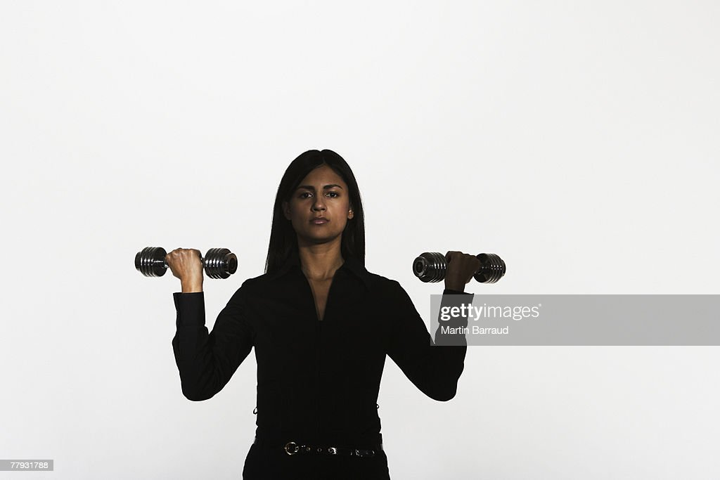 Woman holding two small free weights : Stock Photo