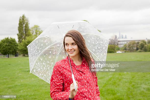 Woman holding umbrella in rain in urban park.