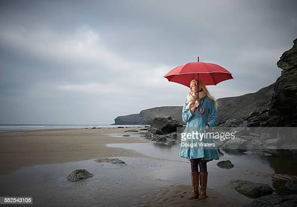 Woman holding umbrella on rocky beach.
