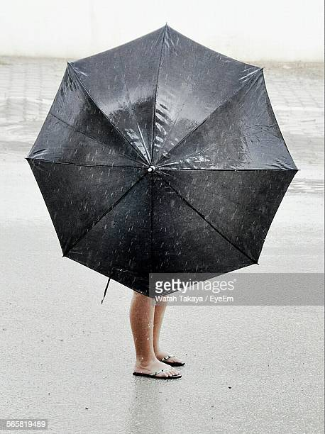 Woman Holding Umbrella While Standing At Beach In Rainy Season