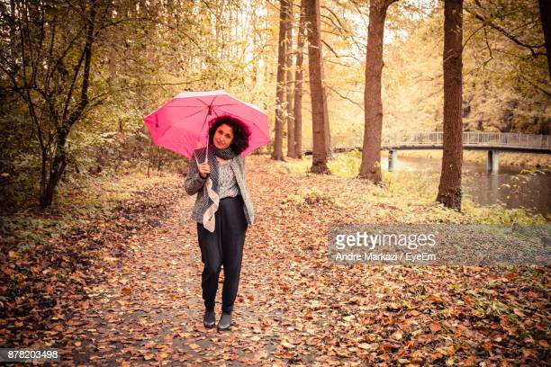 Woman Holding Umbrella While Standing At Park During Autumn