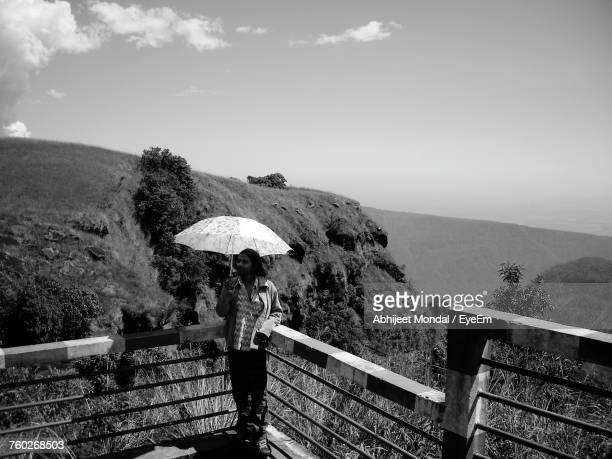 Woman Holding Umbrella While Standing By Railing Against Sky