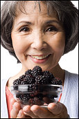 woman holding up a bowl of blackberries