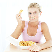 woman holding up a potato wedge from a box