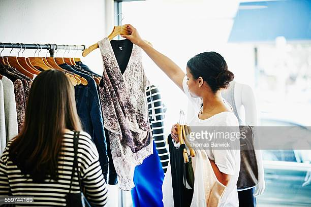 Woman holding up blouse in clothing boutique