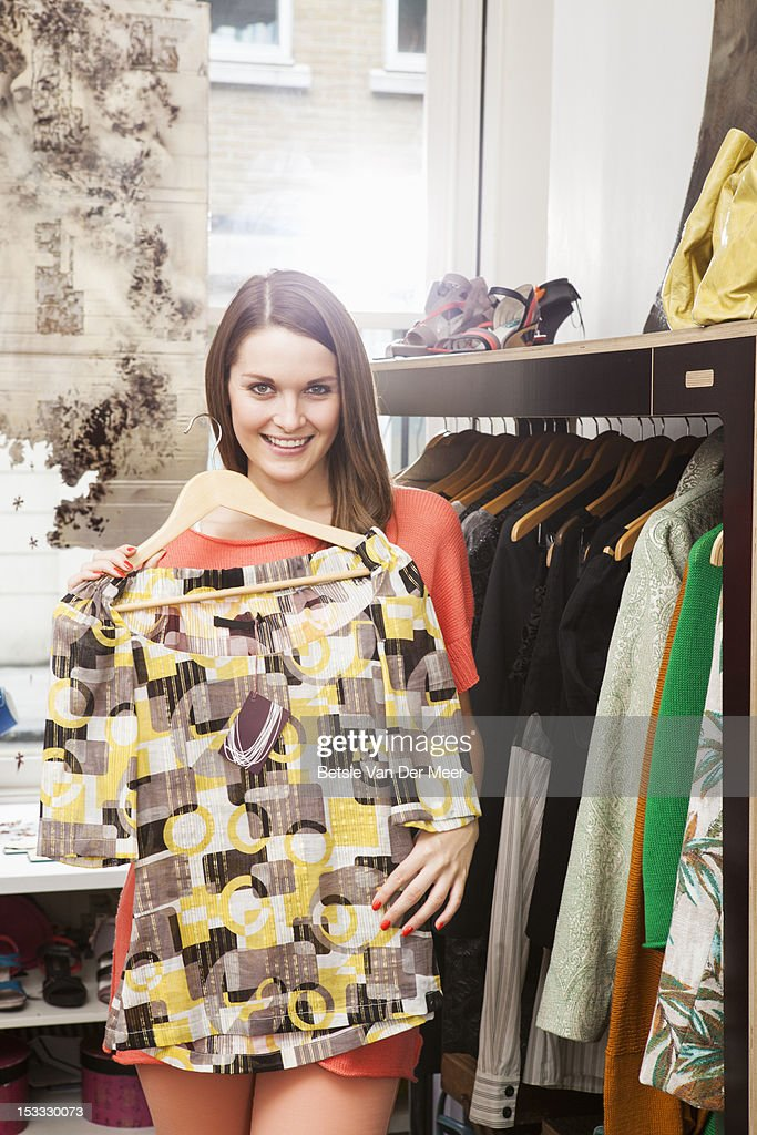 Woman holding up blouse in fashion shop. : Stock Photo