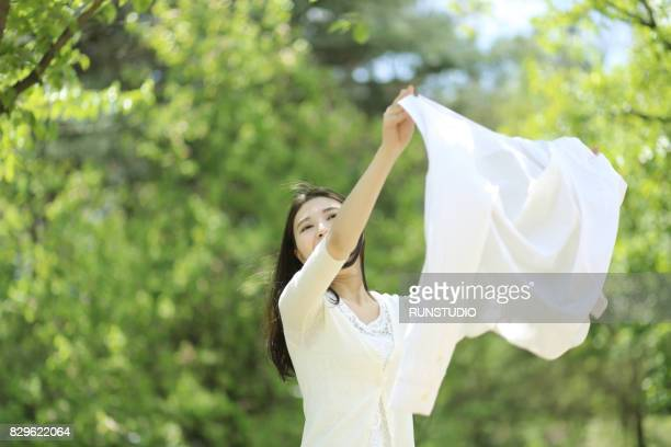 Woman holding up clean white shirt to blow in the wind