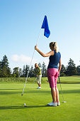 Woman holding up flag for other golfer