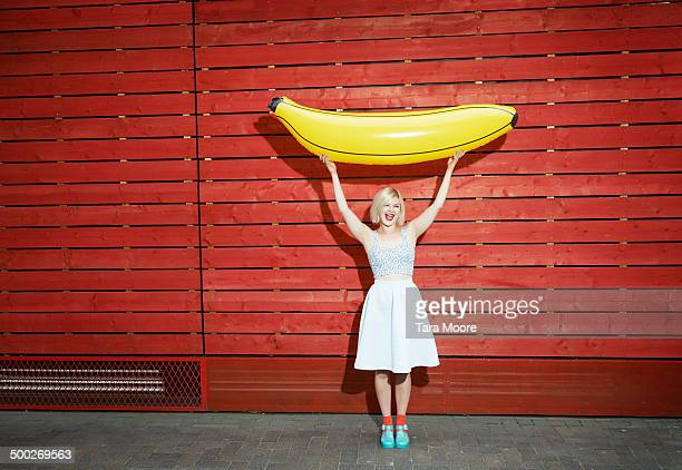 woman holding up giant toy banana
