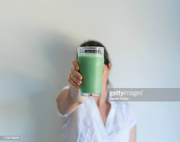 Woman holding up glass of fresh vegetable juice