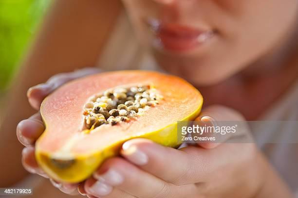 Woman holding up halved papaya