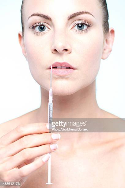 Woman holding up syringe