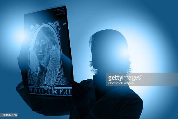 Woman holding up x-ray of a dollar bill