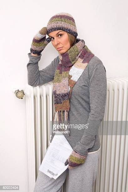 Woman leaning against heater holding bill, portrait
