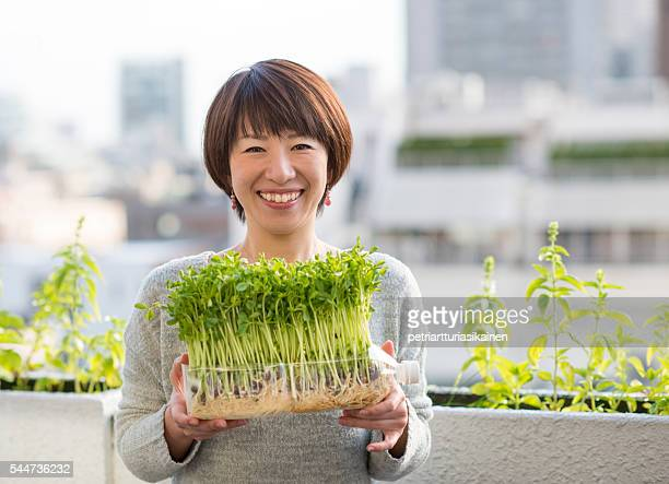 Woman holding vegetables growing in plastic bottle