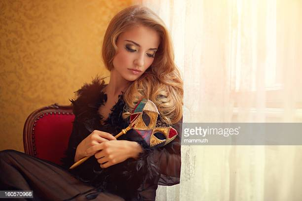 woman holding venetian mask