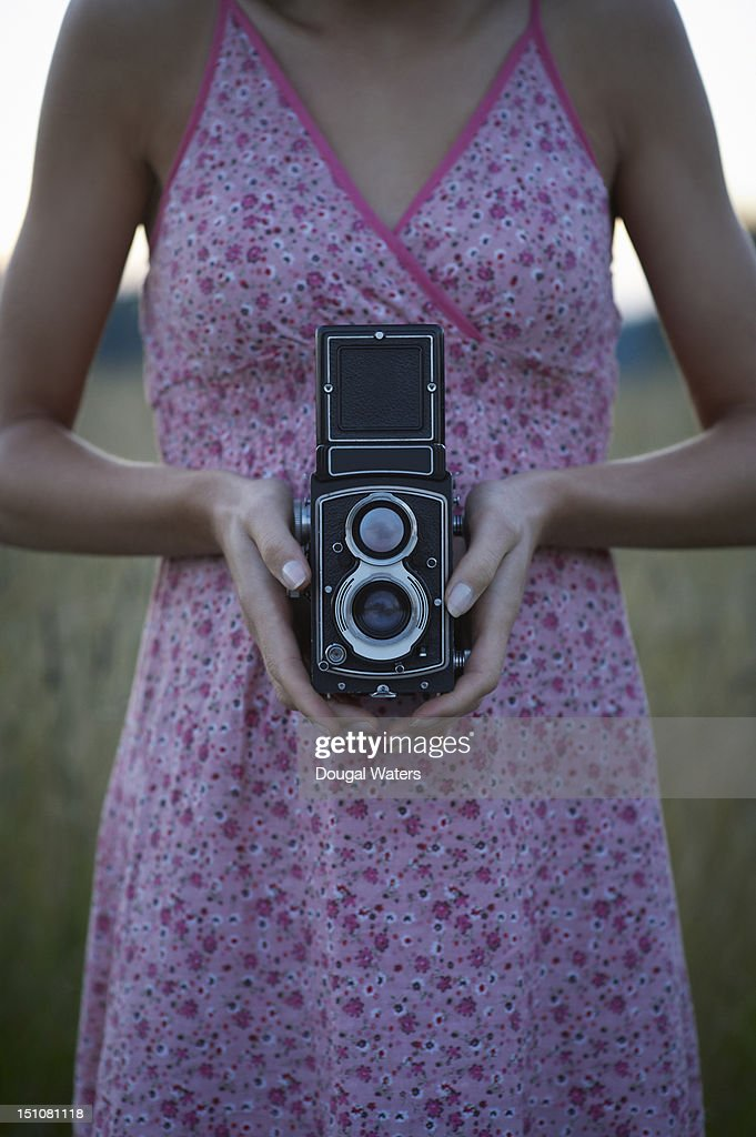 Woman holding vintage camera in countryside. : Stock Photo
