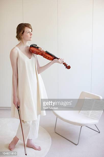 持つ女性がバイオリンを演奏