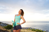 Athletic woman holding water bottle in front of sunset by the sea