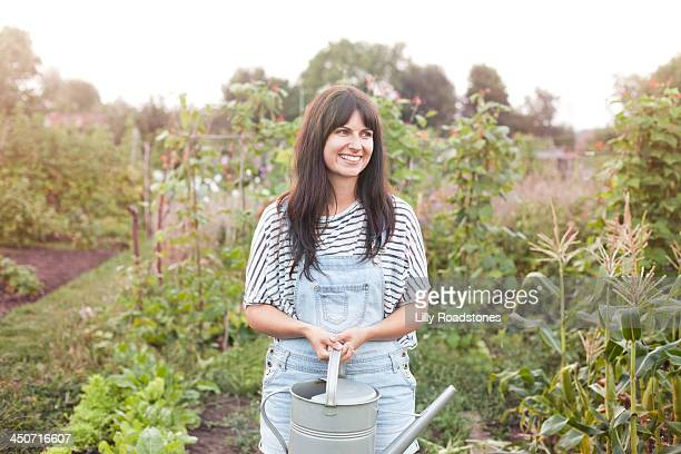 Woman holding watering can on allotment