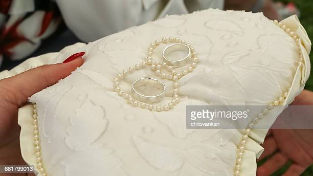 woman holding wedding rings on heart shaped pillow