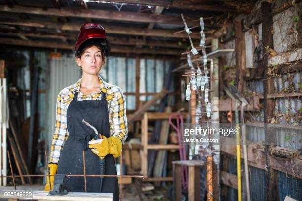 Woman holding welder in workshop