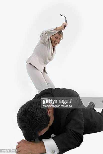 Woman holding whip and standing over businessman lying on floor