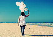 woman holding white balloons and walking on seaside