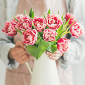 Spring flowers arrangement. Woman in pastel pink apron and blue linen shirt holding white enamel vase with fresh pink tulips. Florist shop, Womans day greeting card concept, square crop