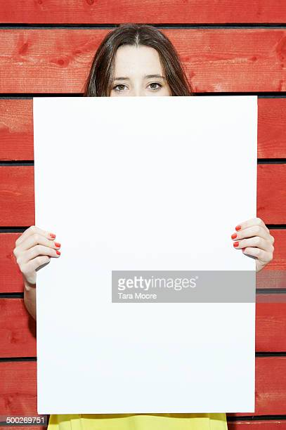 woman holding white message board