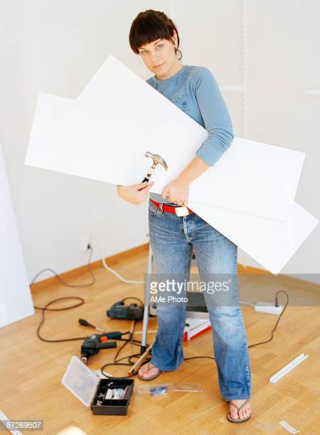 A woman holding white shelves and a hammer, looking at the camera.
