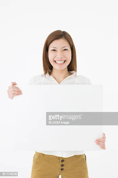 Woman holding whiteboard, smiling