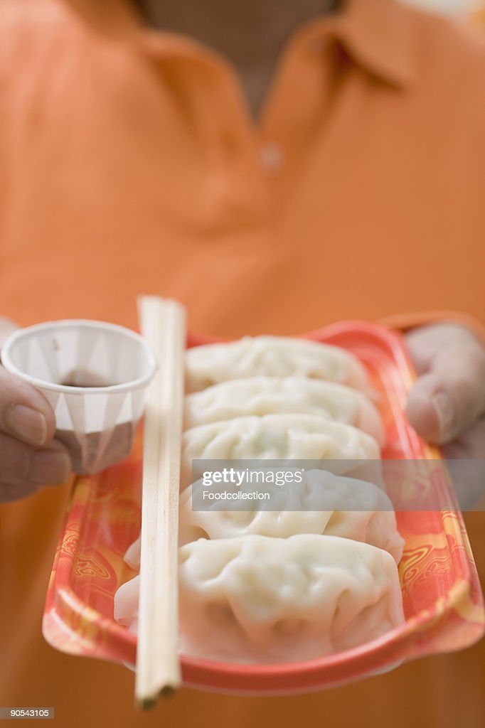 Woman holding wontons on plastic tray, close up, mid section : Stock Photo